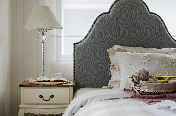 a understated color palette is combined with classic details to create graceful charm in this bedroom the tall scalloped headboard in rich gray velvet is