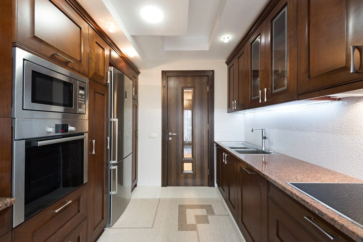 The Burnished Cognac Cabinets And Door Could Tend To Weigh Down This Narrow Kitchen But A Creative Designer Solved That Issue By Drawing The Eye Upward To