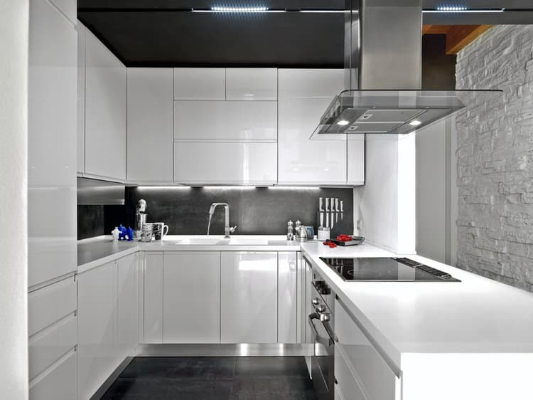High-gloss laminate cabinets clash (in a good way) with a painted stone  wall. The deep mahogany floors and ceiling dilute the white and ground the  space, ...