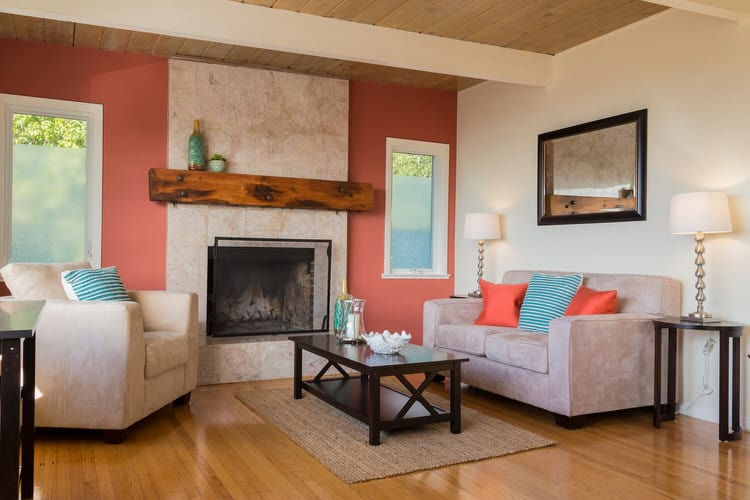 aqua blue and orange silk pillows contrast quite well with the rust accent wall and warm oak flooring to create a relaxing contemporary living room - Blue And Orange Living Room Design