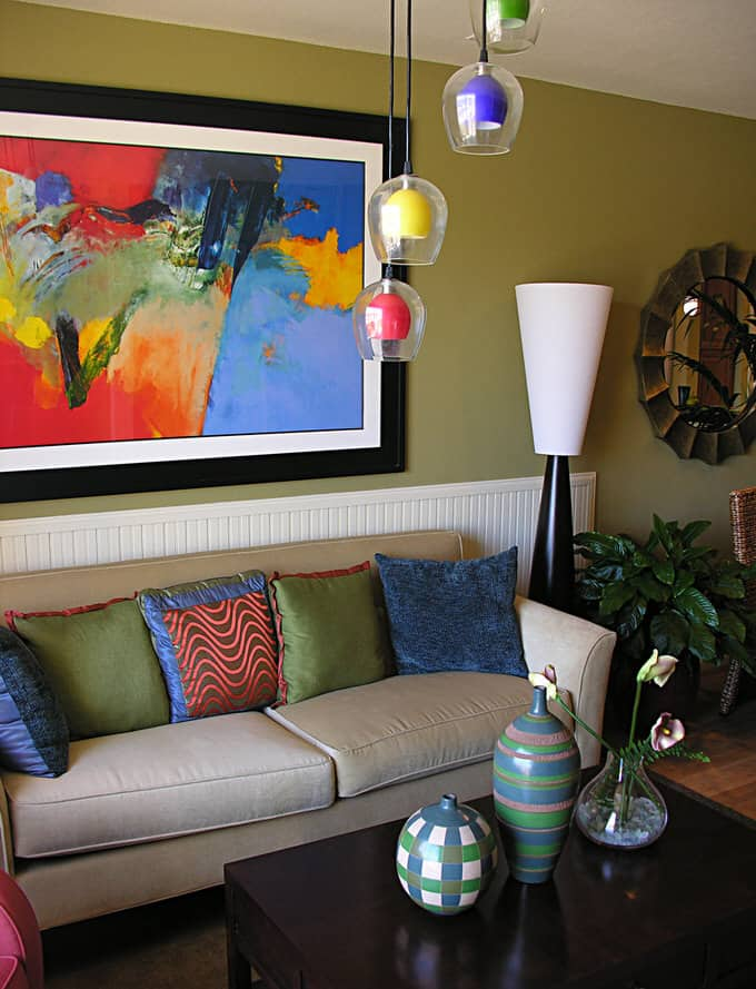 A neutral sofa in this living room is topped with pillows in saturated  colors reflecting the hues of the bold abstract painting.