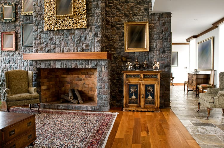 A Rugged Stone Wall Adds Loads Of Character To This Traditional Living  Space. The Dark Gray Slate Is An Ideal Complement To The Warm Wood  Flooring, ...