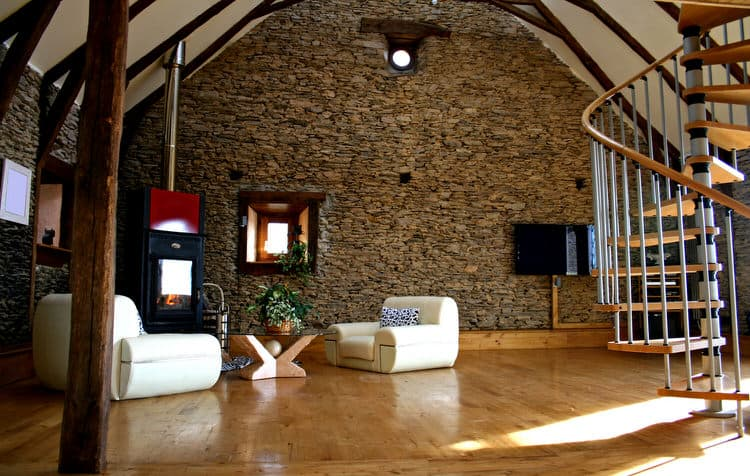 A Stone Wall Stretching To The Peak Of A Cathedral Ceiling Is Definitely  Eye Catching. Adding To The Drama Are White Ceilings Accented With Dark  Wood Beams.